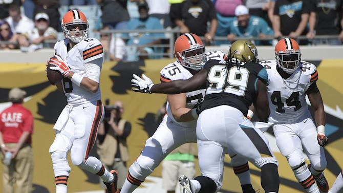 Cleveland Browns quarterback Brian Hoyer, left,  throws a pass during the first half of an NFL football game against the Jacksonville Jaguars in Jacksonville, Fla., Sunday, Oct. 19, 2014. Hoyer completed just 16 of 41 passes for 215 yards and threw a late interception as the Browns lost to the previously winless Jaguars. (AP Photo/Phelan M. Ebenhack)