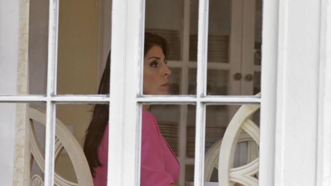 Jill Kelley sits inside her home Tuesday, Nov 13, 2012 in Tampa, Fla. Kelley is identified as the woman who allegedly received harassing emails from Gen. David Petraeus' paramour, Paula Broadwell. She serves as an unpaid social liaison to MacDill Air Force Base in Tampa, where the military's Central Command and Special Operations Command are located. (AP Photo/Chris O'Meara)
