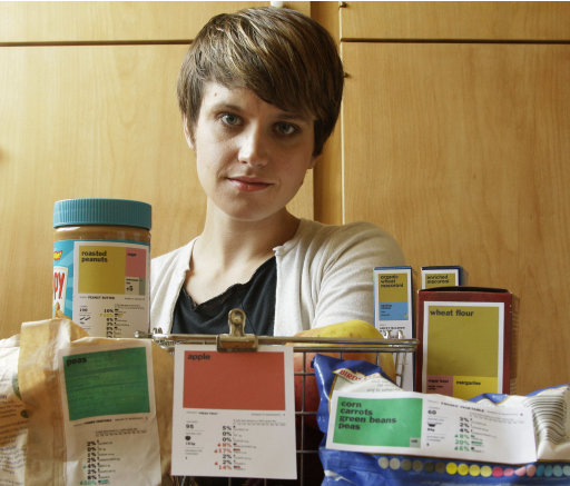 "In this Aug. 10, 2011 photo, designer Renee Walker poses next to her food label samples in San Francisco. Nutrition and design experts want to overhaul the ""nutrition facts"" panel found on packaged foods to make it easier to understand what a food's value is _ and hopefully, make healthier choices."