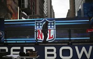A worker walks on a stage in front of the NFL logo in New York's Times Square