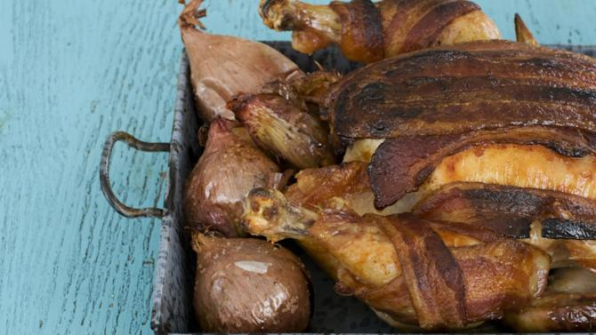 In this image taken on February 11, 2013, roasted chicken with 40 cloves of garlic and a bacon blanket is shown in Concord, N.H. (AP Photo/Matthew Mead)