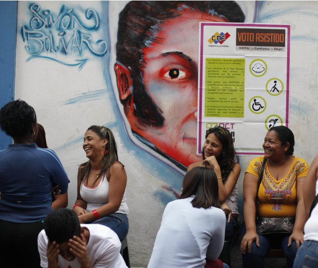 Venezuelans line up in front of mural of Bolivar before casting their vote during the presidential elections in Caracas
