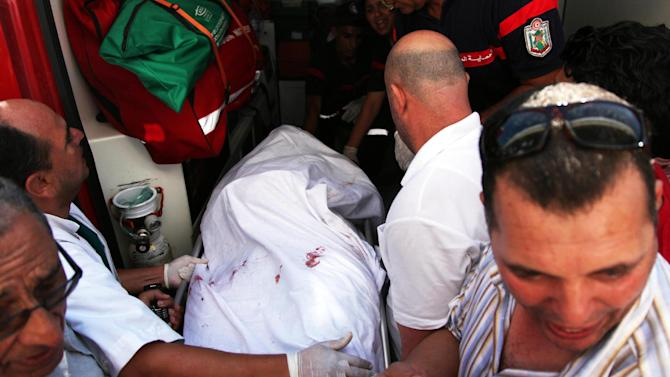 In this photo dated Thursday, July 25, 2013, the body of Tunisian opposition politician Mohammed Brahmi is carried into an ambulance at Mahmoud Materi hospital, north of Tunis, Tunisia. Mohammed Brahmi was shot 14 times in front of his home within sight of his family on Thursday, plunging the country into a political crisis and unleashing demonstrations around the country blaming the government for the assassination. (AP Photo)