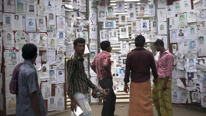 "People look at portraits of missing garment workers from the collapse of a garment factory building plastered on the doors of a school-turned-morgue Saturday, May 4, 2013 in Savar, near Dhaka, Bangladesh. The death toll in the accident rose to more than 530 on Saturday, a day after the country's finance minister downplayed the impact of the disaster on the garment industry, saying he didn't think it was ""really serious."" (AP Photo/Wong Maye-E)"