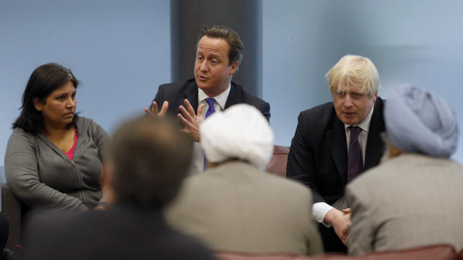 British Prime Minister David Cameron, centre,  and London Mayor Boris Johnson, right,  speak to members of the local community, Thursday, May 23, 2013, during a visit to Woolwich, southeast London where an attack took place on Wednesday. Britain was coming to terms with an apparent return of terrorism to its capital Thursday as new information emerged about the killing of a British soldier near an army barracks in Woolwich by suspected Islamic radicals. (AP Photo/Sang Tan, Pool)