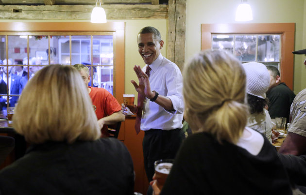 President Barack Obama holds his beer as he greets local patrons during an unscheduled visit to the Common Man Restaurant, Saturday, Oct. 27, 2012 in Merrimack, N.H. (AP Photo/Pablo Martinez Monsivais