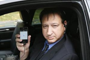 Limousine driver Shuki Zanna holds up his iPhone displaying transportation app Uber as he waits for customers in Beverly Hills