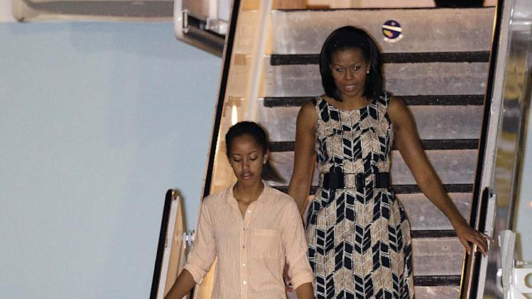 President Barack Obama arrives with first lady Michelle Obama, top, and daughters Malia, top left, and Sasha, bottom right, at Honolulu Joint Base Pearl Harbor-Hickam in Honolulu, for the start of their holiday vacation, Saturday, Dec. 22, 2012. (AP Photo/Gerald Herbert)
