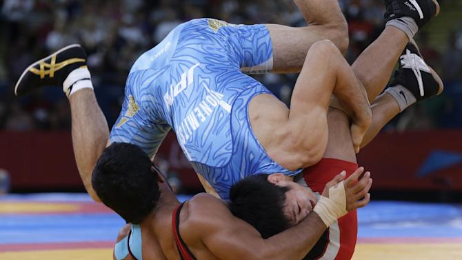 Sushil Kumar of India competes with Tatsuhiro Yonemitsu of Japan (in blue) during their 66-kg freestyle wrestling gold medal match at the 2012 Summer Olympics, Sunday, Aug. 12, 2012, in London. (AP Photo/Paul Sancya)