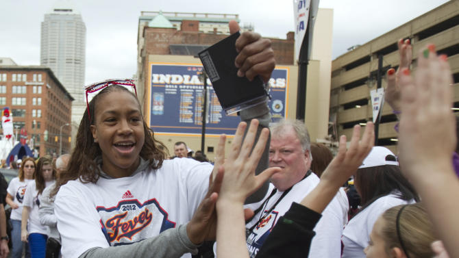Indiana Fever's Tamika Catchings, MVP of the WNBA Finals, celebrates with fans during a celebration event at Bankers Life Fieldhouse on Tuesday, Oct. 23, 2012, in Indianapolis. The team and several thousand fans moved their party indoors to the fieldhouse as morning rain scrapped plans for a parade. The Fever wrapped up the title Sunday night, beating the Minnesota Lynx three games to one. (AP Photo/The Indianapolis Star, Robert Scheer) NO SALES