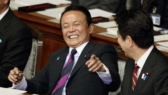 Japan's Finance Minister Taro Aso, left, has a light moment with Prime Minister Shinzo Abe during a plenary session at the lower house of parliament in Tokyo, Thursday, Feb. 28, 2013. Abe vowed to push ahead with more aggressive monetary easing with the nomination Thursday of Asian Development Bank President Haruhiko Kuroda to head Japan's central bank. (AP Photo/Junji Kurokawa)
