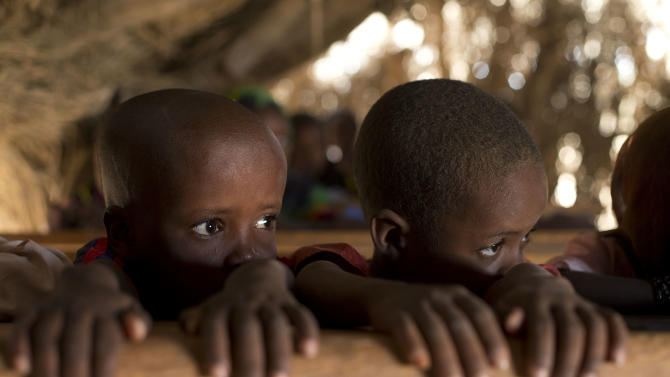 In this Nov. 2, 2012 photo, young students Youssouf, left, and Mahamat, struggle to pay attention during class, in the village of Louri, in the Mao region of Chad. A survey conducted in the country found that 51.9 percent of the children are stunted, one of the highest rates in the world, according to a summary published by UNICEF. Stunting is the result of having either too few calories, too little variety, or both. The struggle that is on display every day in the village's one-room schoolhouse reveals not only the staggering price that these children are paying, but also the price that it has exacted from Africa. (AP Photo/Rebecca Blackwell)