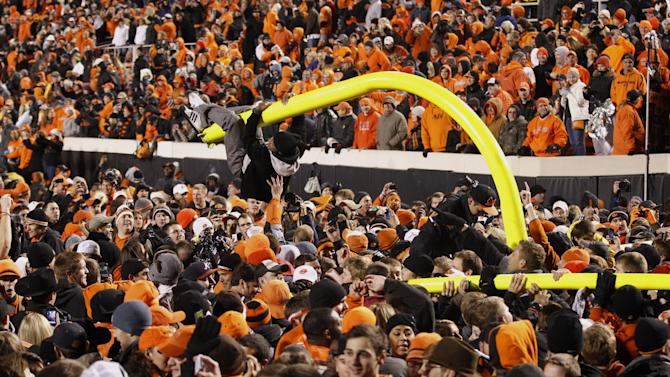 A fan hangs from a goal post after it was torn down in celebration of Oklahoma State's 44-10 win over Oklahoma in an NCAA college football game in Stillwater, Okla., Saturday, Dec. 3, 2011. (AP Photo/Sue Ogrocki)