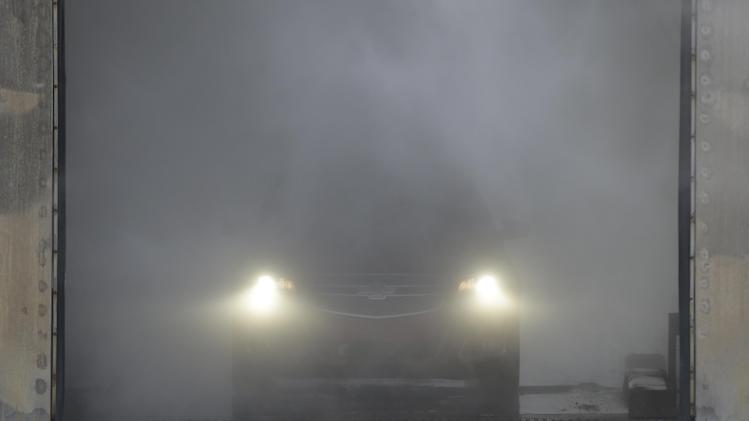 "In a Jan. 17, 2013 photo, a Chevrolet Malibu emerges from a salty mist bath at the General Motors Milford Proving Grounds in Milford, Mich.  It's in this northwest Detroit suburb that GM has its testing facility, which, according to GM consumer affairs chief James Bell, exists for the purpose of beating ""the heck out of a vehicle before the customer can."" Founded in 1924, the 4,000-acre Milford Proving Grounds was the first dedicated automotive testing facility in the world, and remains one of the largest to this day. (AP Photo/Carlos Osorio)"