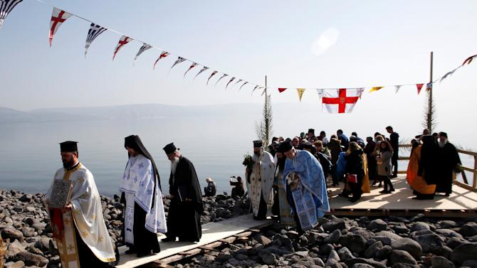 Greek Orthodox priests and worshippers make their way at the end of a ceremony marking the feast of the Epiphany along the shore of the Sea of Galilee