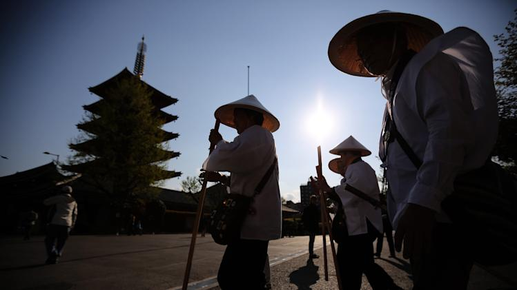 AP10ThingsToSee - A group of pilgrims walk together at the Sensoji Buddhist temple in the Asakusa district of Tokyo on Monday, April 14, 2014. Asakusa is an old town in the capital that draws many tourists from across the world. (AP Photo/Eugene Hoshiko)