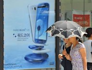 Pedestrians walk past a shop offering South Korea's Samsung Electronics's Galaxy S III phone along a street in Seoul on July 27, 2012. Samsung, the world's biggest technology firm in revenue terms, has reported a record operating profit in April-June of 6.72 trillion won