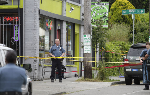 A Seattle Police officer stands outside a cafe where a shooting took place, Wednesday, May 30, 2012. A gunman opened fire at the cafe in Seattle's University district Wednesday, killing two people and critically wounding three others. Police are searching for the gunman, described as a man in his 30s wearing dark clothes. (AP Photo/Ted S. Warren)