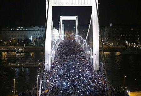 Tens of thousands of Hungarians hold up their mobile phones as they march across the Elisabeth Bridge during a protest against new tax on Internet data transfers