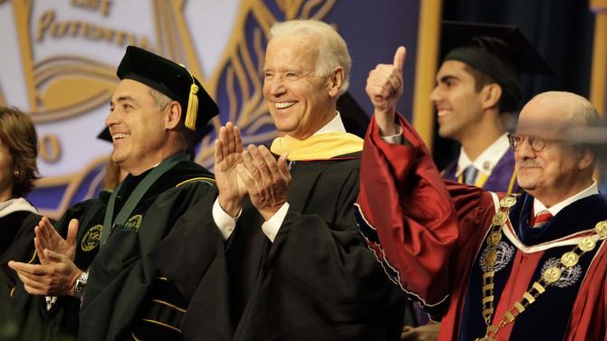"""Vice President Joe Biden, center, smiles after arriving for a graduation ceremony at the Miami Dade College in Miami, Saturday, May 3,2014. Biden said a """"constant, substantial stream of immigrants"""" is important to the American economy, urging citizenship for immigrants living in the U.S. illegally. (AP Photo/Javier Galeano)"""