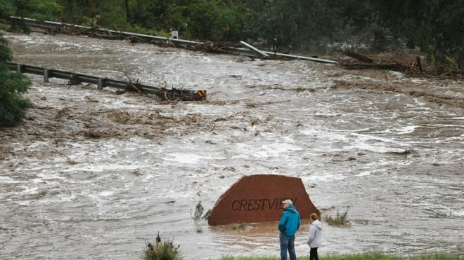 Residents look over a road washed out by a torrent of water near Left Hand Canyon, south of Lyons, Colo.