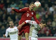 Bayern Munich's midfielder Thomas Mueller (C) and Leverkusen's defender Philipp Wollscheid (R) vie for the ball during the German first division Bundesliga match between FC Bayern Munich and Bayer 04 Leverkusen in Munich, southern Germany. Bayer Leverkusen claimed a shock 2-1 win at Bayern Munich
