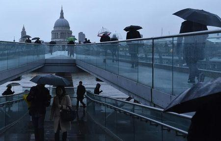 City workers cross the Millennium footbridge at dawn in front of St Paul's Cathedral in London
