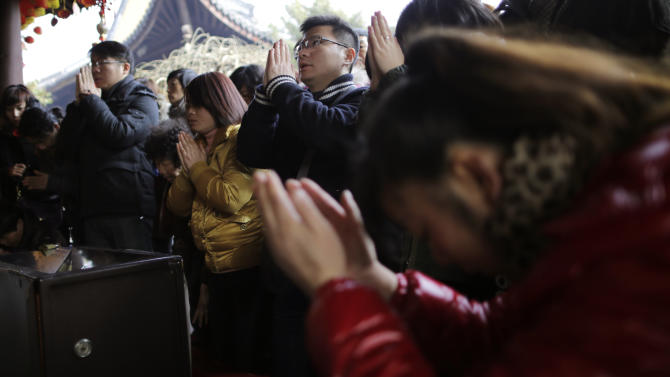 People pray at Longhua Temple on the first day of the Lunar New Year in Shanghai, China on Sunday, Feb. 10, 2013.  Millions across China are celebrating the arrival of the Lunar New Year, the Year of the Snake, marked with a week-long Spring Festival holiday.   (AP Photo/Eugene Hoshiko)