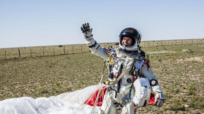 In this photo provided by Red Bull Stratos, Pilot Felix Baumgartner of Austria celebrates after successfully completing the final manned flight for Red Bull Stratos in Roswell, N.M., Sunday, Oct. 14, 2012.Baumgartner came down safely in the eastern New Mexico desert minutes about nine minutes after jumping from his capsule 128,097 feet, or roughly 24 miles, above Earth. (AP Photo/Red Bull Stratos, Balazs Gardi)