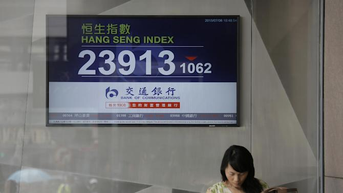 A woman stands in front of a screen showing the Hong Kong share index outside a local bank in Hong Kong, Wednesday, July 8, 2015. The Hang Seng Index dropped in morning trading following more big losses on mainland markets. Chinese stocks led a slump in Asian markets on Wednesday as the sell-off in Shanghai intensified and Greece's future in the euro remained highly uncertain. (AP Photo/Vincent Yu)