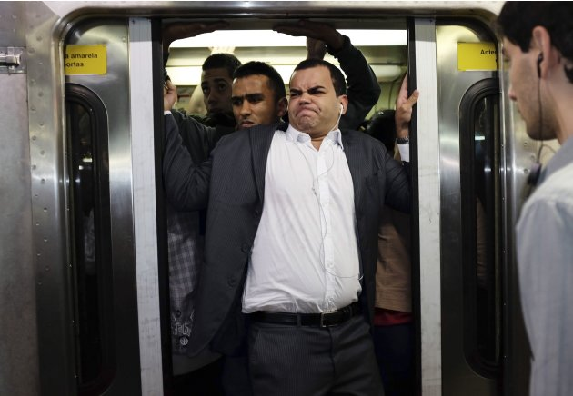 A commuter tries closing the door of a crowded train at a subway station in downtown Sao Paulo