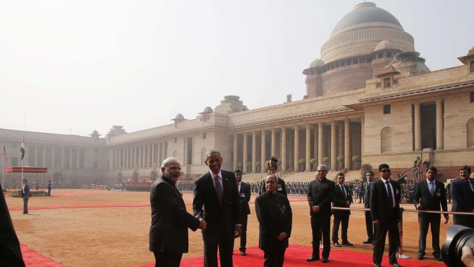 U.S. President Obama shakes hands with India's PM Modi as they stand with President Mukherjee in front of the Rashtrapati Bhavan presidential palace in New Delhi