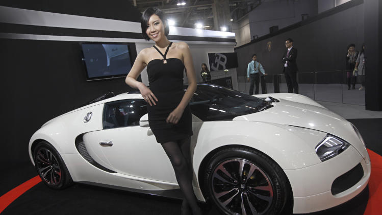 In this photo taken on Thursday, Nov. 24, 2011, a model poses in front of a Bugatti super car during a super car show in Macau. China's superrich want supercars. That's what the makers of world's most exotic and expensive sports cars are hoping as they gather in Macau this week for the first Asian edition of Monaco's annual Top Marques show that began eight years ago. (AP Photo/Vincent Yu)