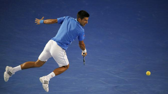 Novak Djokovic of Serbia jumps to hit a return against Milos Raonic of Canada in their men's singles quarter-final match at the Australian Open 2015 tennis tournament in Melbourne