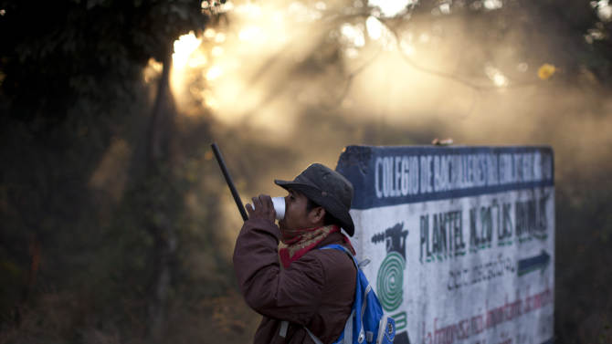 An armed and masked man takes a sip of coffee as he guards a roadblock at the entrance to the community of El Pericon near Ayutla, early Saturday, Jan. 19, 2013. Hundreds of  men in the southern Mexico state of Guerrero have taken up arms to defend their villages against drug gangs, a vigilante movement born of frustration at extortion, killings and kidnappings in a region wracked by violence. (AP Photo/Dario Lopez-Mills)
