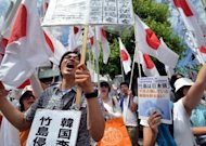Japanese nationalists raise national flags in Tokyo to protest against a visit by South Korean President Lee Myung-Bak on August 10 to disputed islands known as Takeshima in Japan and Dokdo in Korean. The visit infuriated Japan, which recalled its ambassador from Seoul. Tokyo also cancelled a finance ministers&#39; meeting this month and said it would review a foreign exchange swap agreement