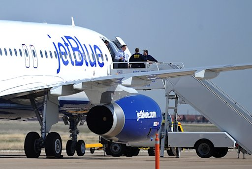 Authorities board JetBlue flight 191, which was headed from New York to Las Vegas, after an emergency landing at Rick Husband Amarillo International Airport in Amarillo, Texas, Tuesday, March 27, 2012, when an unruly pilot caused the Las Vegas-bound flight to be diverted. Passengers said the pilot screamed that Iraq or Afghanistan had planted a bomb on the flight, was locked out of the cockpit, and then tackled and restrained by passengers. The pilot who subsequently took command of the aircraft elected to land in Amarillo at about 10 a.m., JetBlue Airways said in a statement.