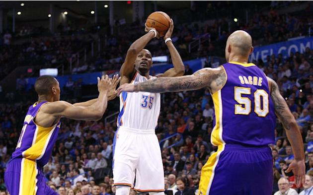 Oklahoma City Thunder forward Kevin Durant (35) shoots between Los Angeles Lakers forward Wesley Johnson (11) and center Robert Sacre (50) during the third quarter of an NBA basketball game in Oklahom