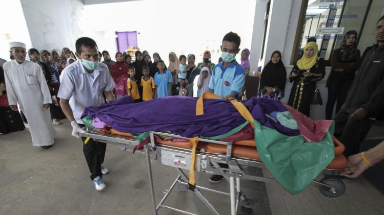 Rescue workers carry the body of a dead teacher to a hospital in Pattani province, south of Thailand, after a roadside bomb attack