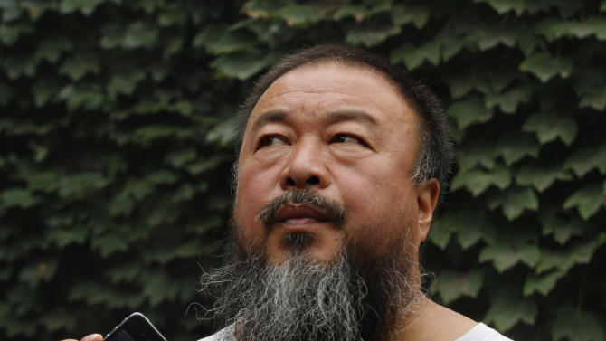 FILE - In this July 20, 2012 file photo, Chinese dissident artist Ai Weiwei listens as his lawyer announces over a speakerphone the verdict of Ai's lawsuit against the Beijing tax authorities in Beijing. Ai said Wednesday, Oct. 31, 2012 he's started returning money to his supporters after exhausting all legal channels to fight a massive tax bill. The supporters gave him the cash after the government levied a $2.4 million tax bill on Ai's design firm last year in what his backers saw as punishment for his activism. (AP Photo/Ng Han Guan, File)
