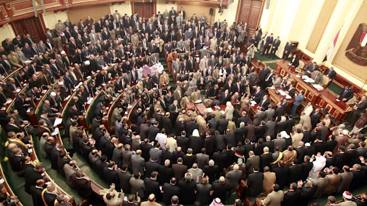 """FILE - In this Monday, Jan. 23, 2012 file photo, members of parliament stand and pray for the souls of the victims who died during the uprising that ousted President Hosni Mubarak during the first Egyptian parliament session after the revolution, in Cairo, Egypt. Egypt's highest court has ordered the country's Islamist-dominated parliament dissolved, saying its election about six months ago was unconstitutional. The Supreme constitutional Court ruled Thursday that a third of the legislature was elected illegally. As a result, it says in its explanation of the ruling, """"the makeup of the entire chamber is illegal and, consequently, it does not legally stand."""" (AP Photo/Asmaa Waguih,Pool, File)"""