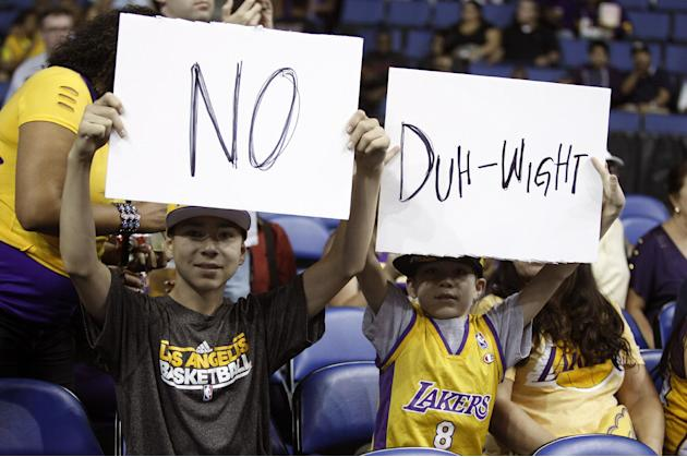 Los Angeles Lakers fans 12-year-old Ian Klock and his 9-year-old brother Nate Klock, both from Upland, Calif., display posters about Dwight Howard, prior to the Lakers' NBA basketball preseason game a