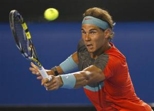 Rafael Nadal of Spain hits a return to Bernard Tomic of Australia during their men's singles match at the Australian Open 2014 tennis tournament in Melbourne