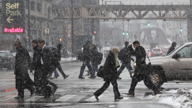 Commuters walk during a snow storm as they arrive in downtown Chicago Tuesday, March 5, 2013. Chicago was hit by a storm expected to dump as much as 10 inches of snow in the area before the end of the day,  the most since the 2011 blizzard and its more than 20 inches of snow. (AP Photo/Kiichiro Sato)