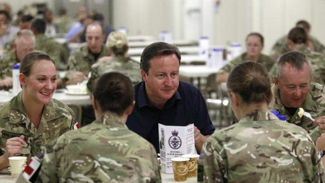 Britain's Prime Minister David Cameron, center, has breakfast with British soldiers  during a visit at Camp Bastion, outside Lashkar Gah, the provincial capital of Helmand province in south Afghanistan, Monday, July 4, 2011. (AP Photo/Lefteris Pitarakis, pool)