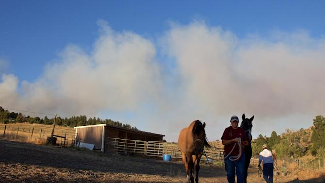 In this Thursday, Aug. 20, 2015 photo, Gale Sheppard evacuates her horses as a wildfire approaches in Prairie City, Ore. In addition to rangeland lost, ranchers and ranching groups say hundreds of cows have perished and millions of dollars' worth of hay stacks and barns has gone up in flames. (Thomas Boyd/The Oregonian via AP) MAGS OUT; TV OUT; NO LOCAL INTERNET; THE MERCURY OUT; WILLAMETTE WEEK OUT; PAMPLIN MEDIA GROUP OUT; MANDATORY CREDIT