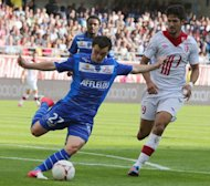 Troyes&#39; French midfielder Julien Faussurier (L) vies with Lille&#39;s Brazilian forward Tulio De Melo (R) during their French L1 football match in Troyes. The match ended in 1-1
