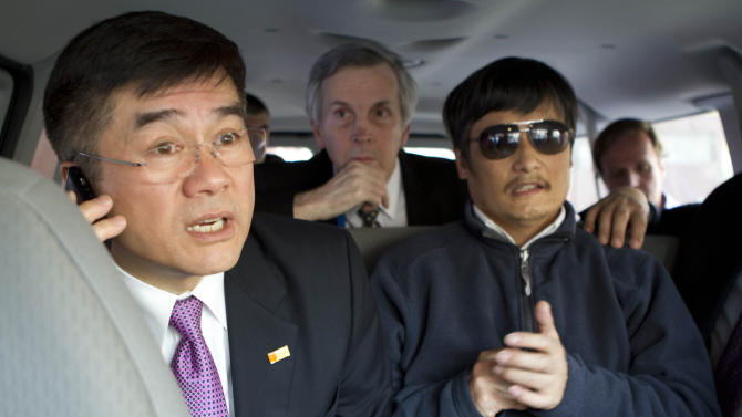 In this photo released by the US Embassy Beijing Press Office, U.S. ambassador to China, Gary Locke, left, makes a phone call as he accompanies blind lawyer Chen Guangcheng, right, in a car en route from the U.S. Embassy to a hospital in Beijing, Wednesday, May 2, 2012. At center is language attache James Brown. (AP Photo/U.S. Embassy Beijing Press Office, HO)