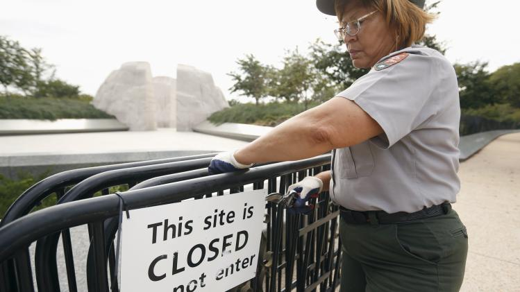 A National Park worker removes a closed sign at the Martin Luther King Jr. Memorial after it was re-opened to the public in Washington