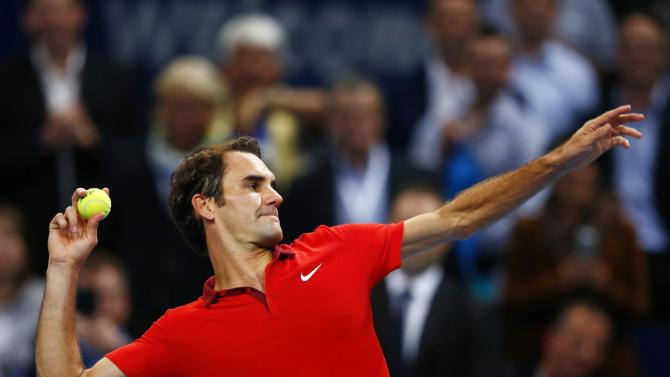 Federer of Switzerland throws a ball after winning against Gilles Muller of Luxembourg at the Swiss Indoors ATP tennis tournament in Basel
